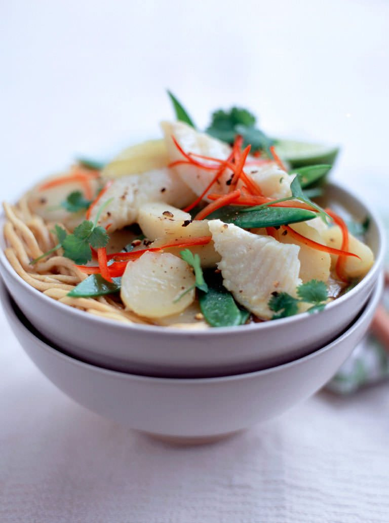 A cup of Asian noodle broth with pangasius